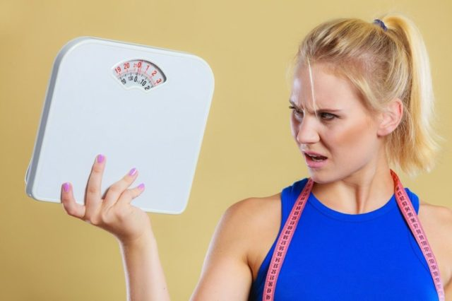 Fit fitness woman with scale. Frustrated angry blonde girl holding weight scales. Time for slimming weightloss diet and healthy lifestyles concept
