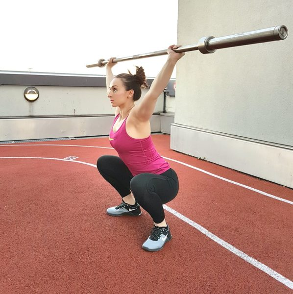 Girl performing an overhead squat during AMRAP workouts.