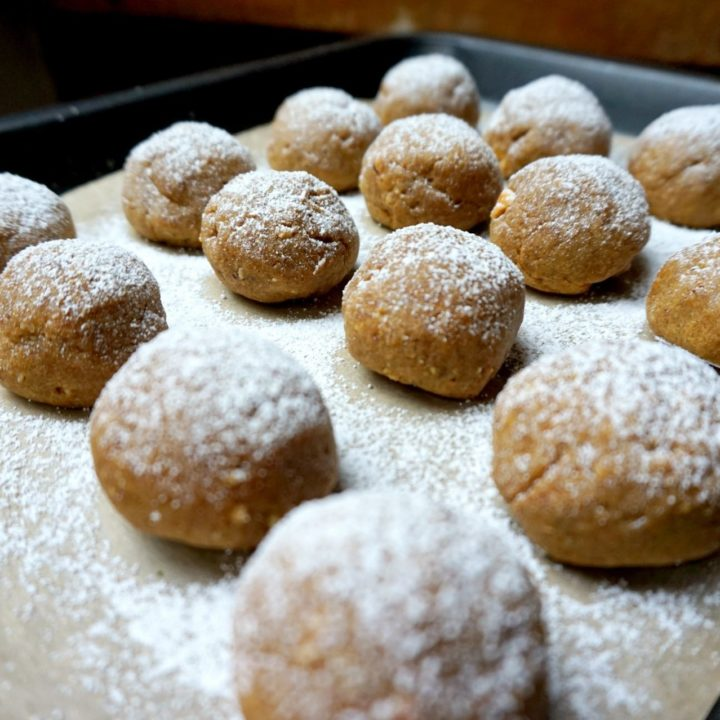 Pumpkin spice cookies sprinkled with powder sugar in a baking tray.