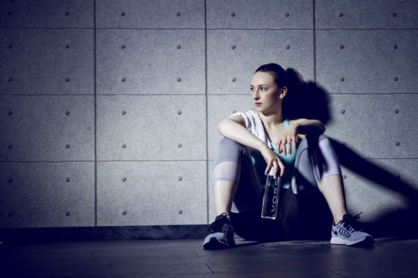 Young woman in sports clothes sitting on the ground after an intense EMOM workout.