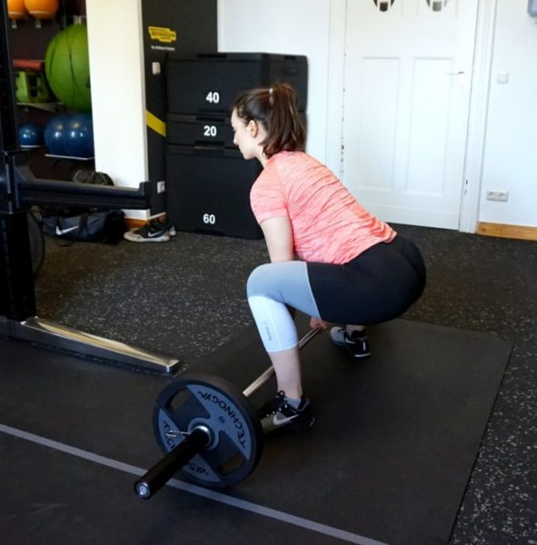 A young woman performing sumo deadlift.