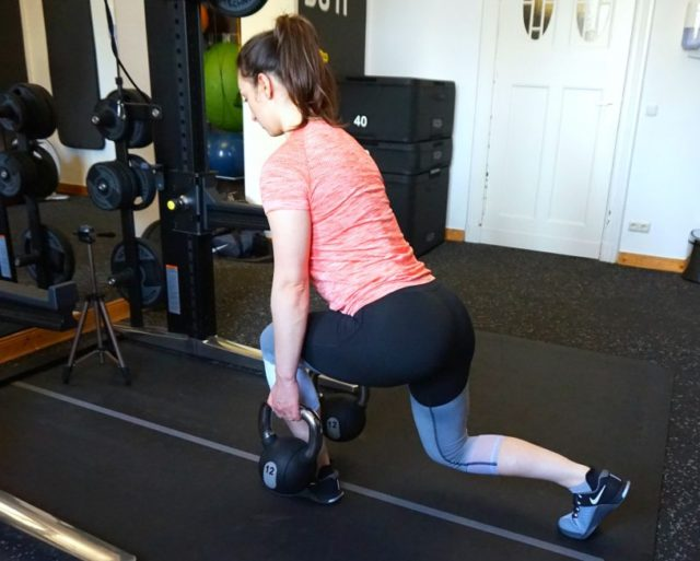 A girl performing a forward-lean reverse lunge.