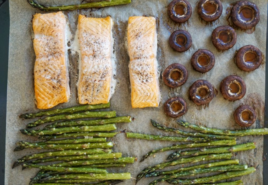 Baked salmon, asparagus and mushrooms on a baking tray.