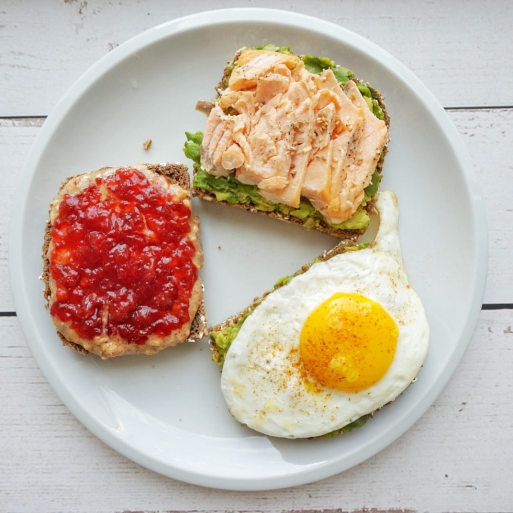 An avocado plus salmon toast, a peanut butter and jelly toast and and egg and an avocado wholewheat toast in a plate.