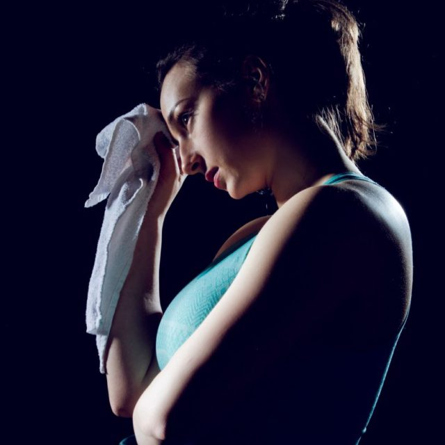 Fit girl wiping her sweat from her forehead with a towel.