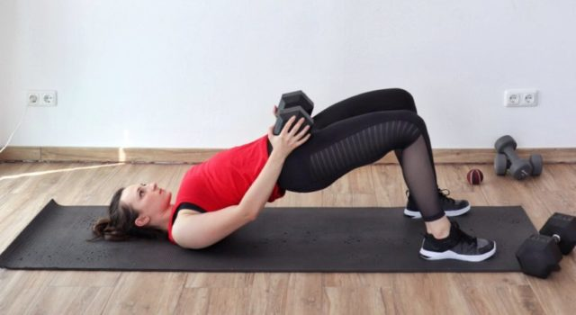 Young woman in sports clothing performing a glutes and legs exercise - glute bridges on a yoga mat using a dumbbell