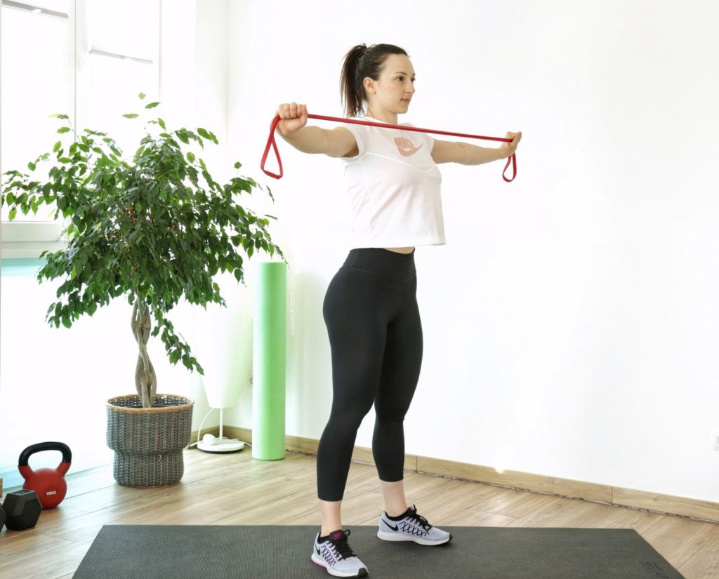 resistance band pull-aparts exercise part of an upper body resistance band home workout