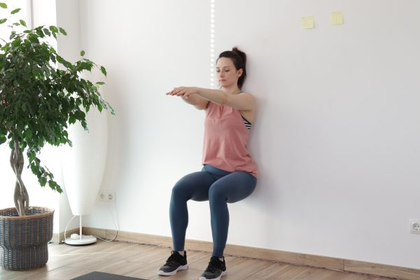 Wallsit bodyweight exercise demonstration by a young woman.