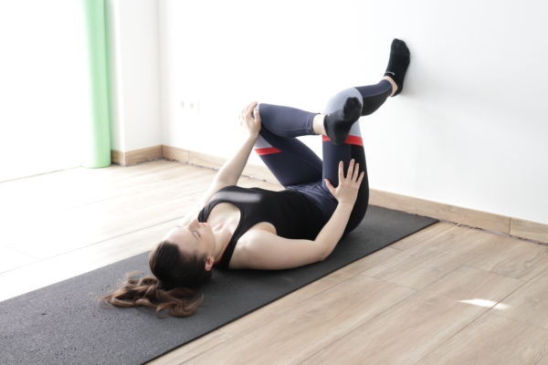 Demonstration of piriformis wall stretch to release tight lower back.
