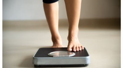 woman stepping on a scale after defying weight loss myths