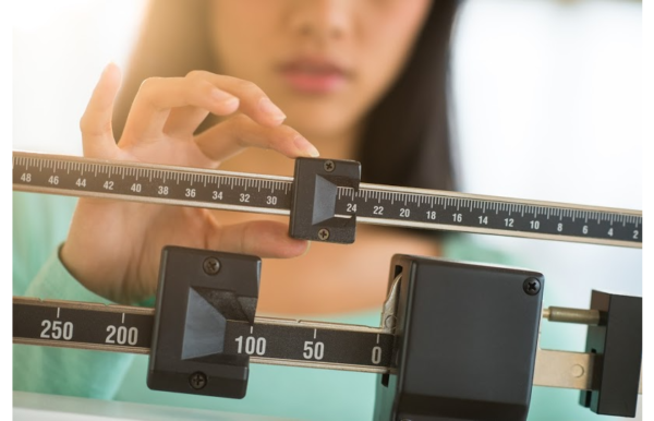 Woman weighing herself to check her weight loss progress.